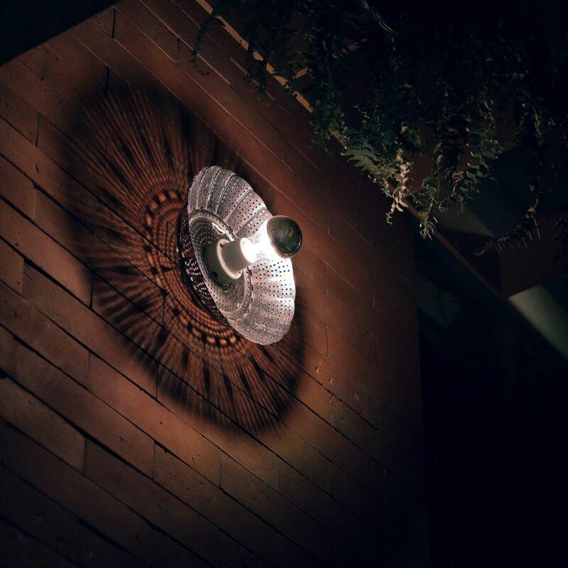 """Decor Urbano Morar Mais 112 Mandala.  Após figurar como peça única na capa do convite da exposição Esculturas de Luz, em 2004, a Mandala tornou-se a primeira escultura seriada do Burgos Studio. O abrir e fechar das """"pétalas"""" da Mandala produz um efeito de luz e sombra que sugere uma tapeçaria ou uma mandala.  Esta luminária é assinada pelo designer Cesar Burgos e integra uma série limitada.  Prazo de envio: Como todas as peças são feitas artesanalmente, pedimos até 20 dias de prazo para que as peças sejam preparadas e entregues aos Correios (não inclui o tempo do frete)."""
